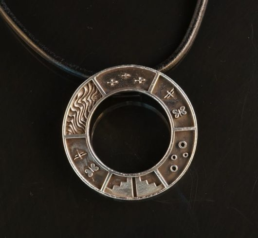 Joe Cajero story pendant: round sterling silver pendant with symbols