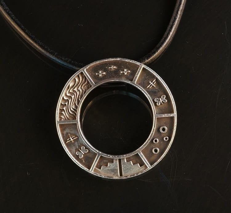 Joe Cajero story pendant: round sterling silver pendant with symbols